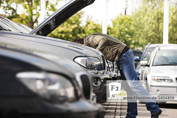 Mann bei Überprüfung Engine Auto Autohändler Mann bei Überprüfung Engine Auto Autohändler