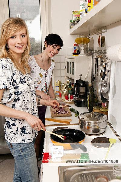 Portrait von zwei jungen Frauen in Küche kochen