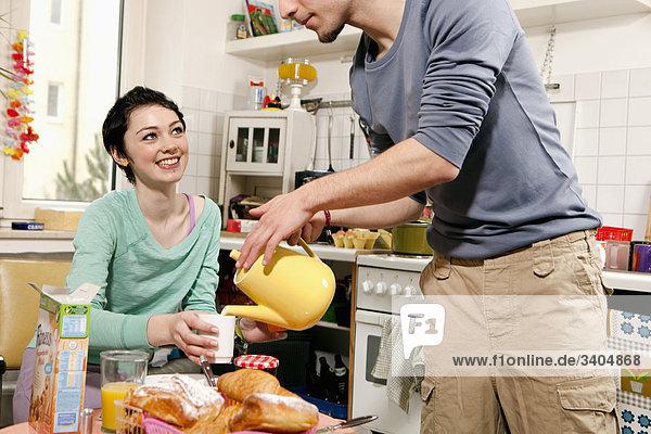 junger Mann Serving Teenagerin am Frühstückstisch