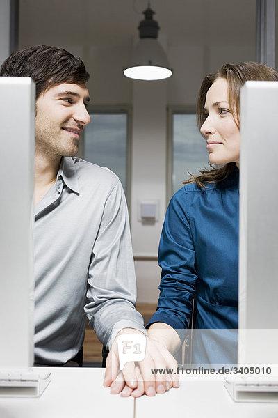 junges paar sitzt hinter Computer im Büro Hände