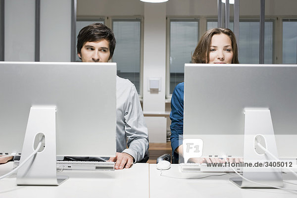 junger Mann Blick auf Kollegin sitzen am Computer im Büro