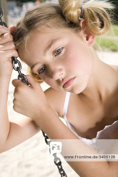 traurig junges Mädchen sitzen auf Swing am Spielplatz