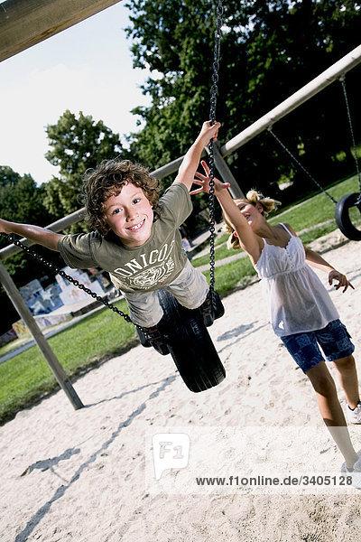Junge auf Swing auf Spielplatz