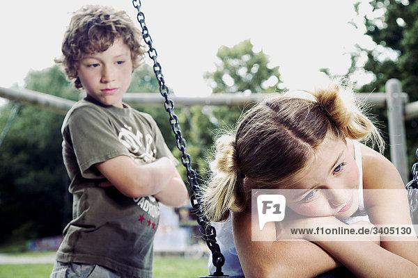 junge beobachten traurig Mädchen am Spielplatz