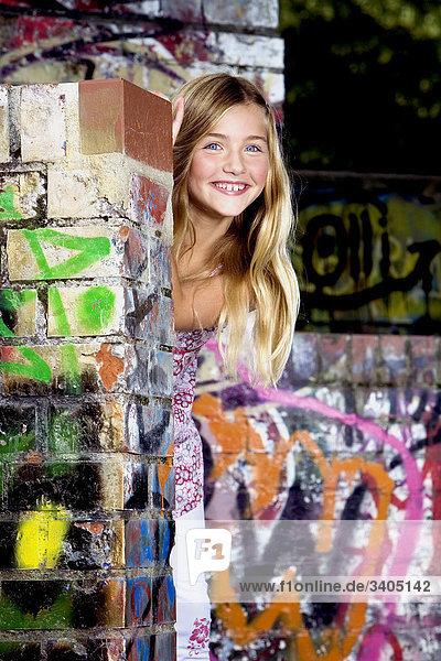 Porträt von blond Mädchen stand hinter Mauer