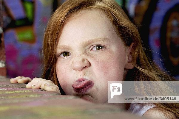 Porträt der jungen Mädchen hinter Mauer Zunge heraus