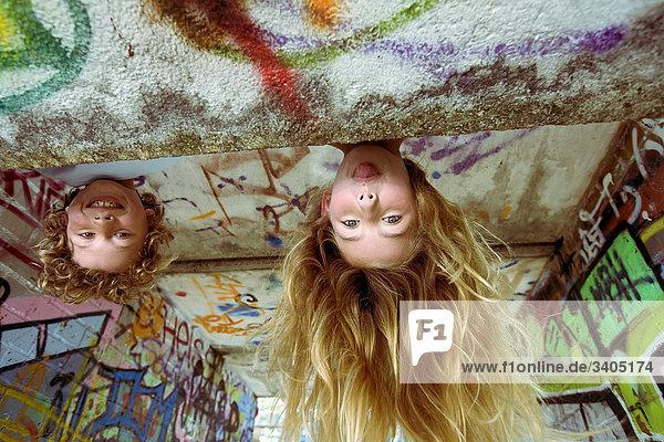 zwei junge Kinder Spielplatz Mädchen Zunge heraus