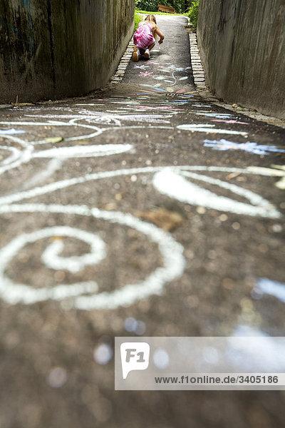 junges Mädchen Malerei Blumen auf Straße mit Buntstiften
