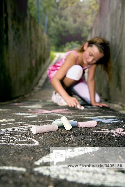 junges Mädchen malen mit Buntstiften auf der Straße