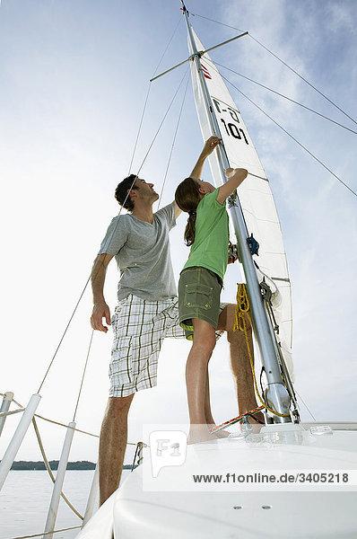 junge Mädchen und Vater auf Schiff Segel festlegen