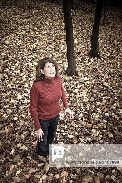Woman standing on fallen leaves in her back yard