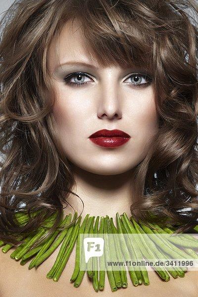 Junge Frau mit einer Kette aus grünen Bohnen mund