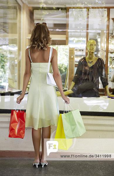 Junge Frau steht mit Einkaufstüten vor einem Schaufenster