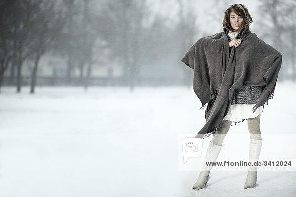 Junge Frau steht mit Poncho im Schnee