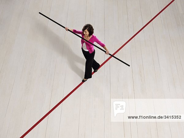 Frau balanciert auf dünner roter Linie