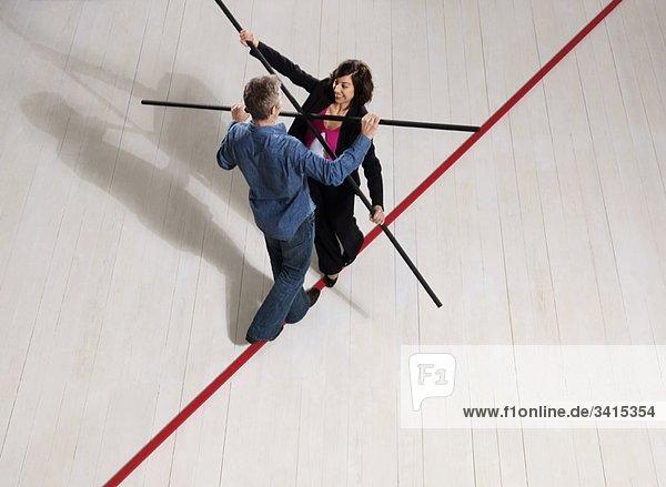 Mann und Frau balancieren auf dünner roter Linie