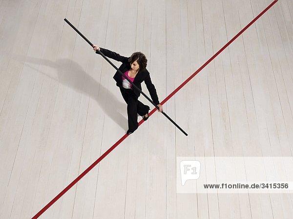 Geschäftsfrau balanciert auf roter Linie