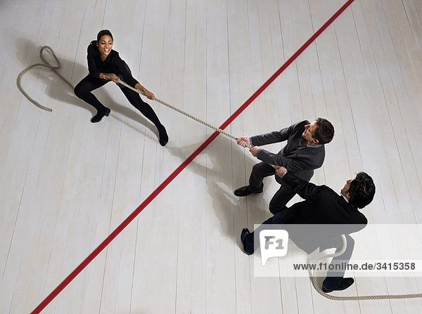 Geschäftsmänner ziehen Frau mit Seil