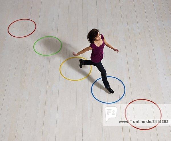Frau springt über Kreise