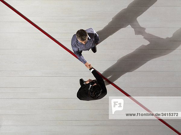 Geschäftsleute Schütteln Hände über rote Linie