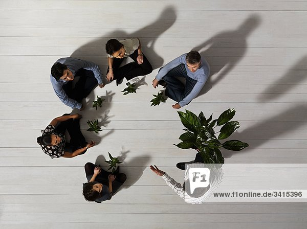 Personengruppe auf dem Boden mit Pflanzen