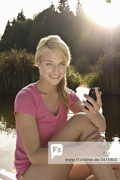 Junge Frau mit Handy  lächelnd.