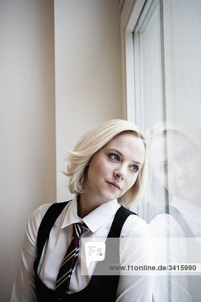 Geschäftsfrau lehnt am Fenster