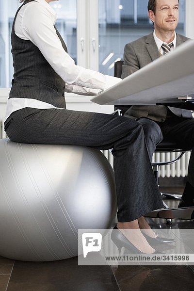Geschäftsfrau auf dem Gymnastikball sitzend