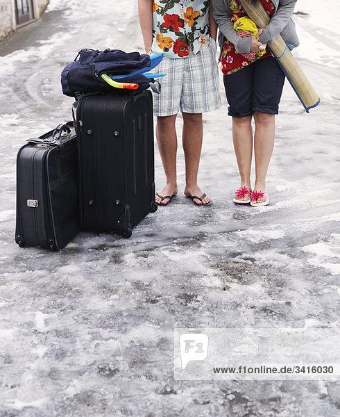 Paar im Schnee stehend mit Koffern