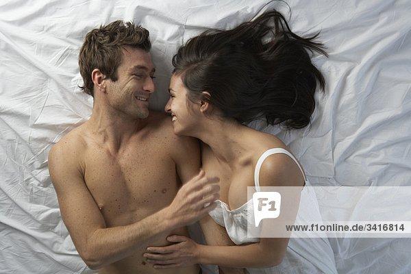 Paar im Bett lachend  hoher Winkel