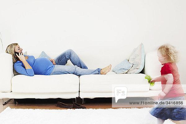 Schwangere Frau am Telefon mit Kleinkind