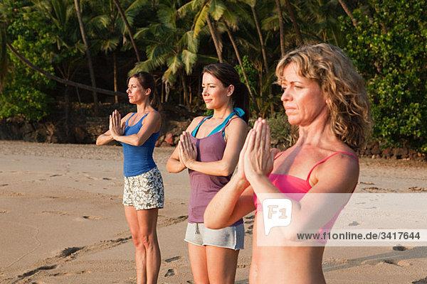 Women practicing yoga on a beach