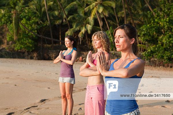 Frauen beim Yoga am Strand