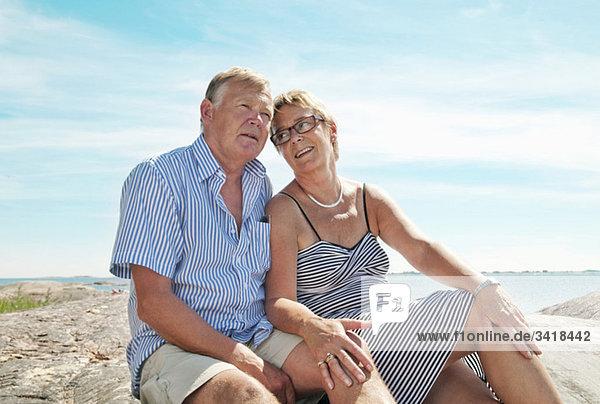 Zwei ältere Menschen am Strand sitzend