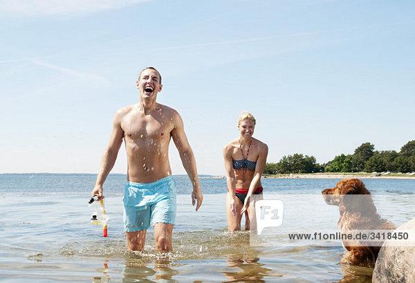 Zwei Menschen und ein Hund im Wasser