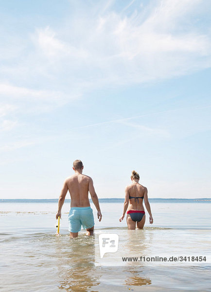 Young couple walking in the water