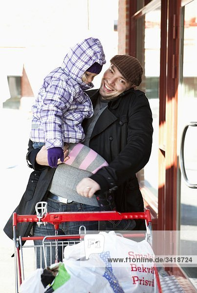 Dad carries daughter when shopping