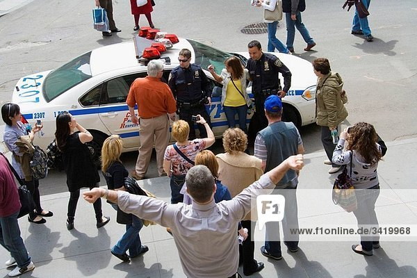 Tourists and police car and cops  Wall Street  New York City  USA