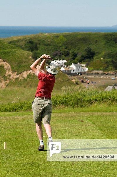 A man playing golf at Porth Dinllaen  Lleyn Peninsula  North Wales UK