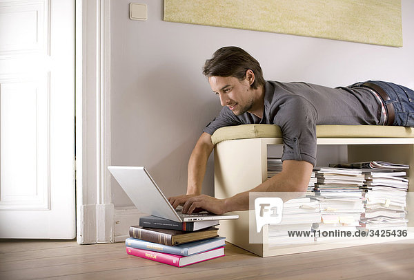 Man lying on a shelf and using a notebook  low angle view