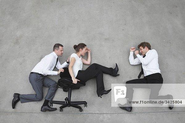 Drei Geschäftsleute  Geschäftsmann schiebend Geschäftsfrau im Bürostuhl  Seitenansicht  erhöhte Ansicht