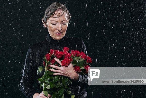 Frau steht im Regen und hält einen Blumenstrauß. Frau steht im Regen und hält einen Blumenstrauß.