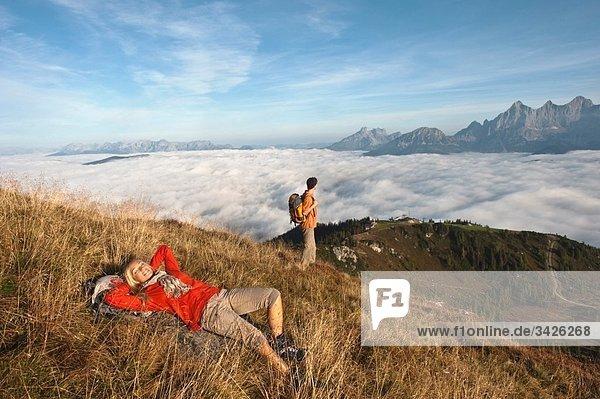 Österreich  Steiermark  Reiteralm  Paar in den Bergen  Frau im Gras liegend