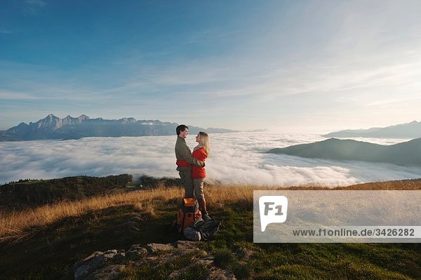 Austria  Steiermark  Reiteralm  Couple of hikers embracing  laughing  side view