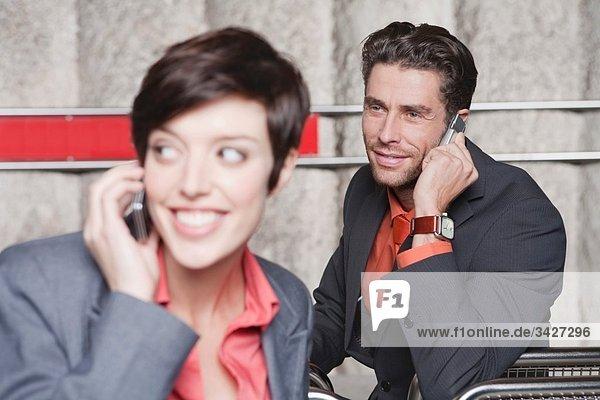 Deutschland  Bayern  München  Geschäftsleute am U-Bahnhof mit Handy  Portrait