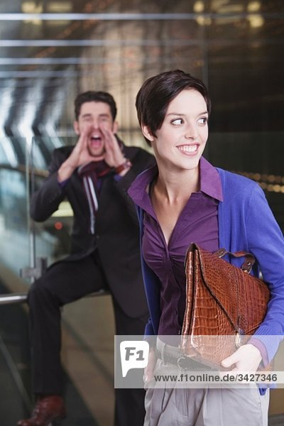 Two business people at subway station  man shouting
