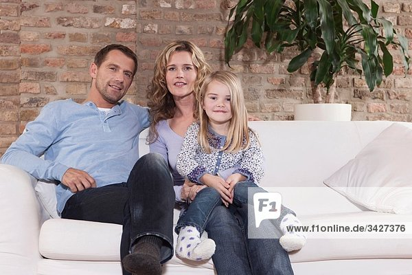 Deutschland  Köln  Familie auf Sofa im Wohnzimmer sitzend  lächelnd  Portrait