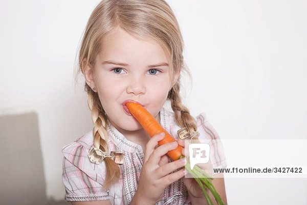 Girl (4-5) with braids eating a carrot  portrait  close-up