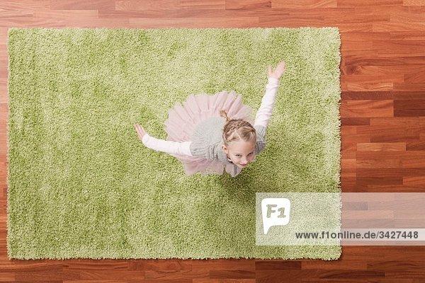 Mädchen (6-7) spielt auf Teppich  schaut nach oben  erhöhte Ansicht Mädchen (6-7) spielt auf Teppich, schaut nach oben, erhöhte Ansicht