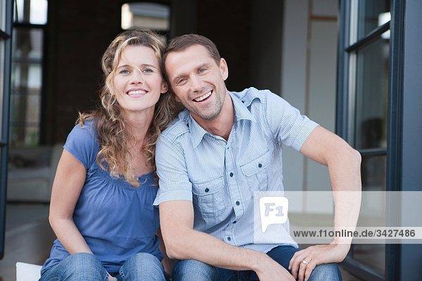 Deutschland  Köln  Paar auf der Terrasse sitzend  lächelnd  Portrait